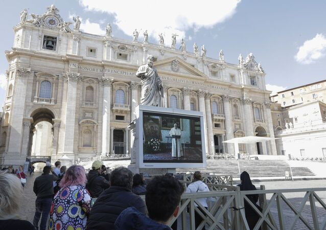 Faithful watch Pope Francis deliver the Angelus prayer on a giant screen to avoid crowds gathering, in St. Peter's Square, at the Vatican, Sunday, 8 March 2020. The pope in his streamed remarks said he was close in prayers to those suffering from the coronavirus and to those caring for them.