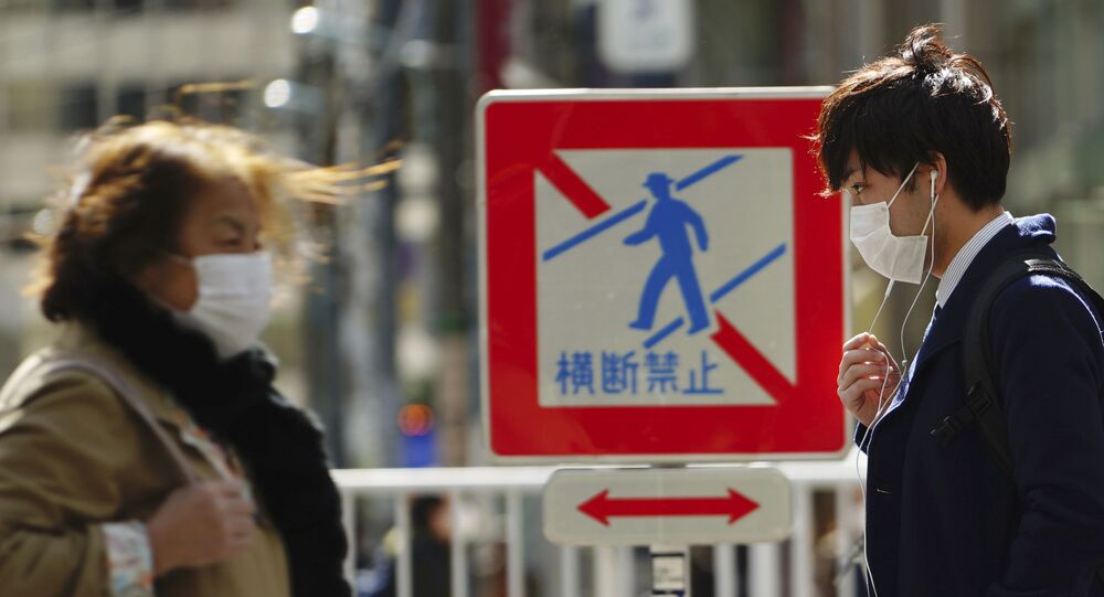 Pedestrians with protective masks on a street Thursday, 5 March 2020, in Tokyo. The number of infections of the COVID-19 disease spread around the globe.