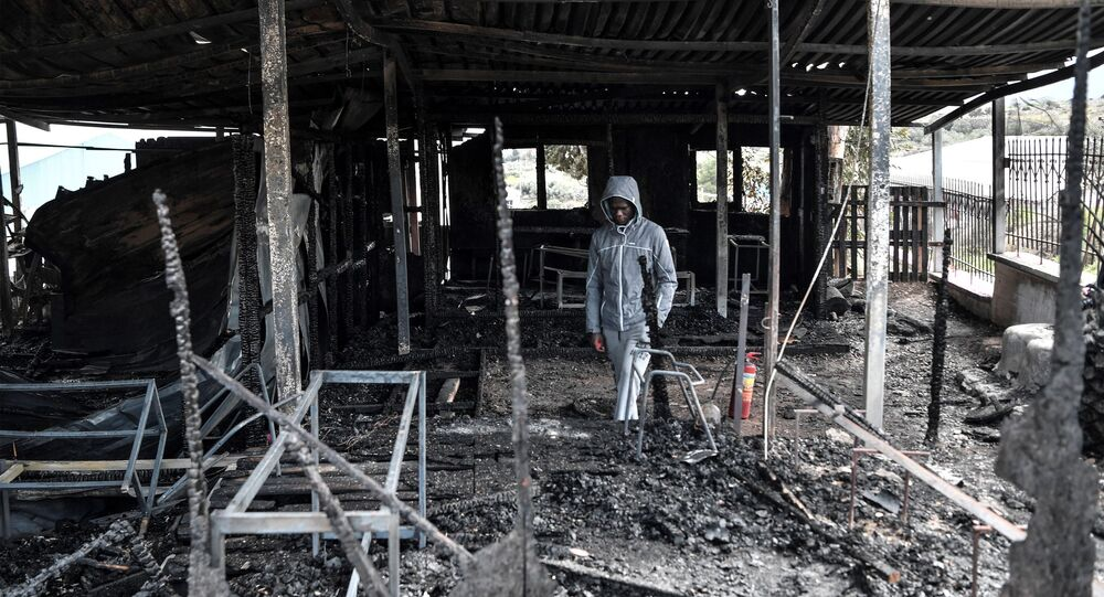 Israel from Congo, a migrant who was also a teacher of the school for refugee children walks through the burnt facilities of the school of the One Happy Family NGO's project on the island of Lesbos on March 8, 2020.