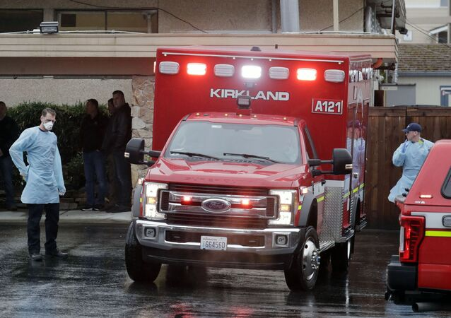 Workers near an ambulance at the Life Care Center in Kirkland, Washington