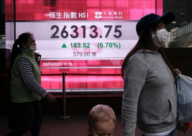 People wear protective masks as they walk past a panel displaying the Hang Seng Index during morning trading following the outbreak of the new coronavirus in Hong Kong, China March 2, 2020