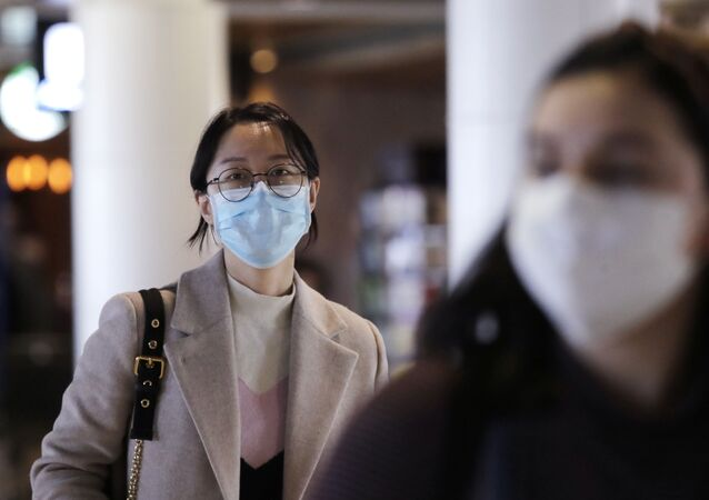 Travelers at Seattle-Tacoma International Airport wear masks Tuesday, March 3, 2020, in SeaTac, Wash. Six of the 18 Western Washington residents with the coronavirus have died as health officials rush to test more suspected cases and communities brace for spread of the disease.