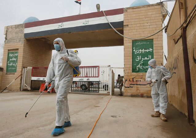 Workers in protective suits spray disinfectants near the gate of Shalamcha Border Crossing, after Iraq shut a border crossing to travellers between Iraq and Iran, Iraq March 8, 2020.