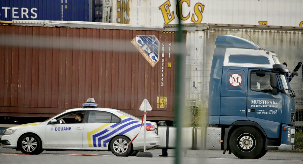A customs police car parks next to a truck waiting to pass through a scanning tunnel at the Port of Zeebrugge, in Zeebrugge, Belgium, Thursday, Oct. 24, 2019. British police raided two sites in Northern Ireland and questioned a truck driver as they investigate the deaths of 39 people found in a truck container that they believe came from Zeebrugge and was then found at an industrial park in southeastern England.