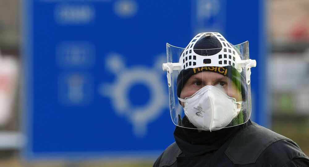 A Czech police officer, with a protective mask, waits during sanitary checks on drivers at the border crossing between Germany and Czech Republic, near the German village of Furth and the Czech village Nova Kubice in a measure to protect against the spread of the novel coronavirus, on March 9, 2020.