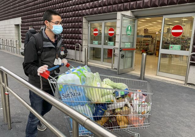 A man wearing a protective mask leaves a supermarket with trolleys full of shopping in Milan on March 8, 2020 as Italy quarantines more than 10 million people around the financial capital Milan and the tourist mecca Venice for nearly a month to halt the spread of the novel coronavirus, COVID-19.