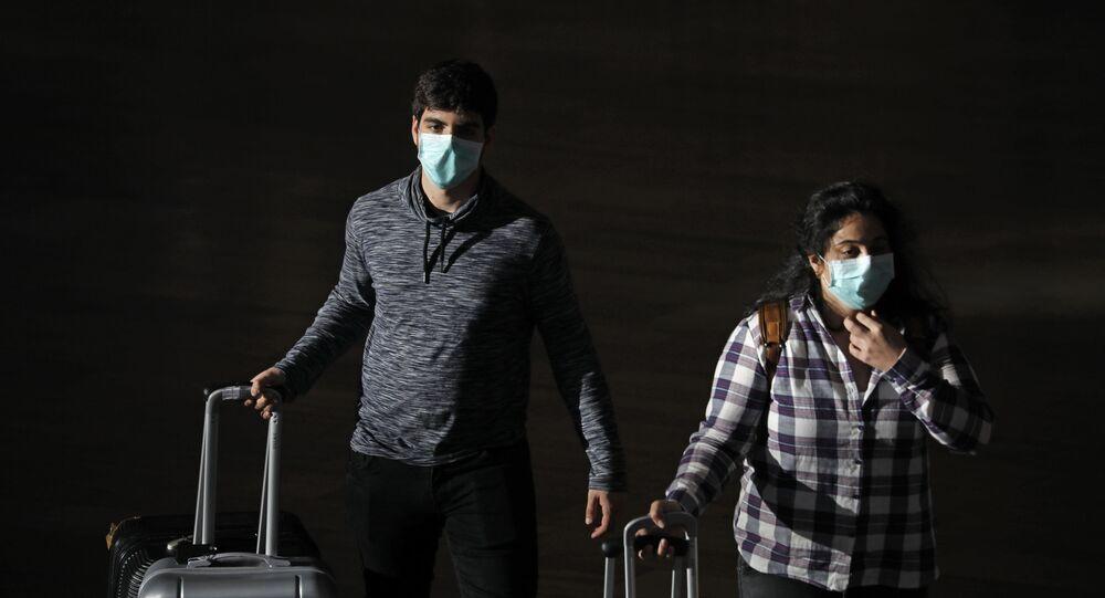 Passengers wear masks to help protect against coronavirus, at the Ben Gurion Airport near Tel Aviv, Israel, Sunday, 8 March 2020.