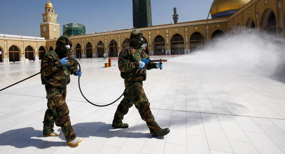 Members of the civil defense team spray disinfectant to sanitize surrounding of the Kufa mosque