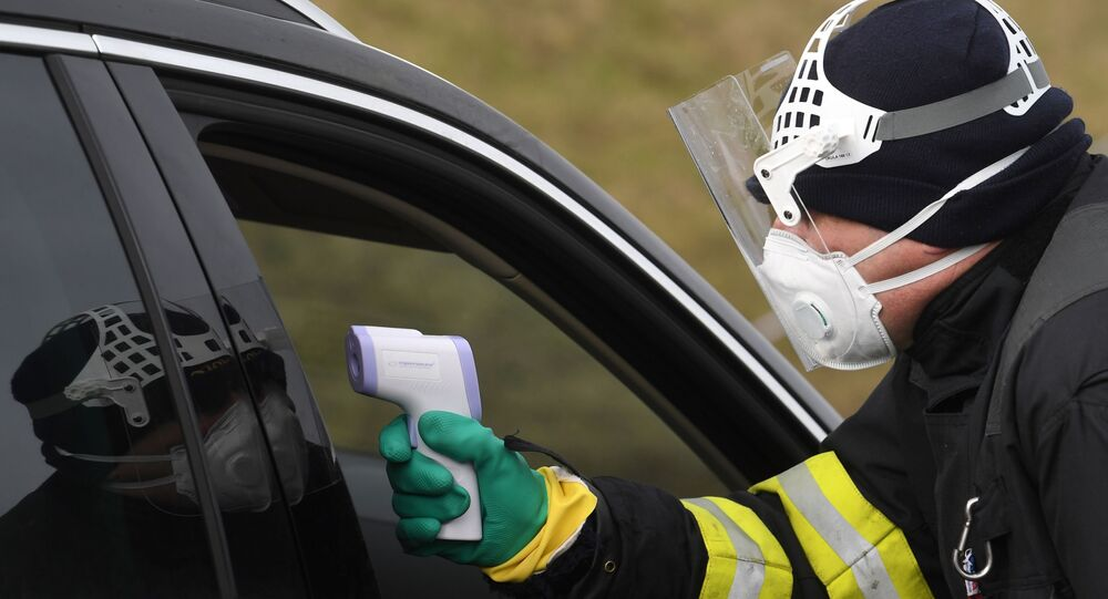A Czech police officer, with a protective mask, checks the temperature of a driver during sanitary checks on drivers at the border crossing between Germany and Czech Republic, near the German village of Furth and the Czech village Nova Kubice in a measure to protect against the spread of the novel coronavirus, on March 9, 2020.