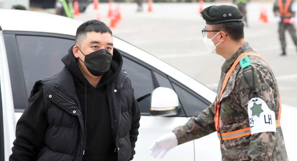 Former BIGBANG boyband member Seungri (L) wearing a face mask arrives at a military boot camp in the border town of Cheorwon, 100 kilometres north of Seoul, on March 9, 2020