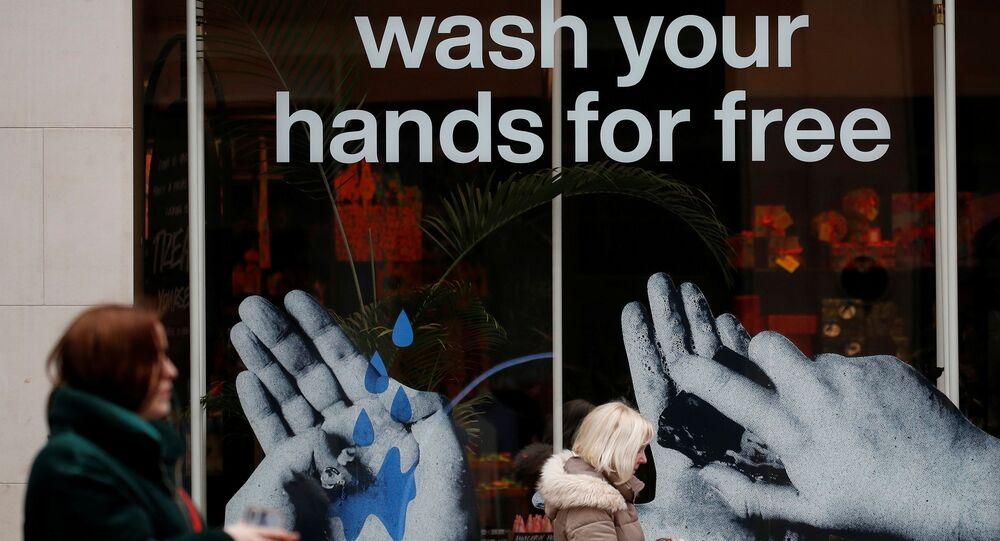 Women walk past a sign in a shop window offering a free hand washing service to customers in Liverpool