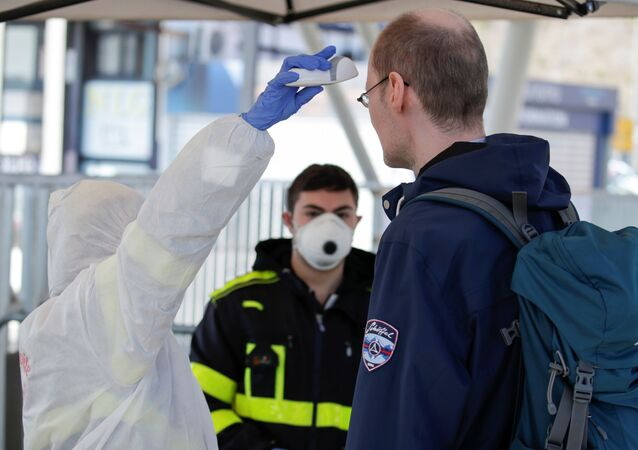 A person wearing a protective suit and mask checks the temperature of people departing from the ferry port of Molo Beverello after Italy orders a countrywide lockdown to try and contain a coronavirus outbreak, in Naples, Italy, March 10, 2020.