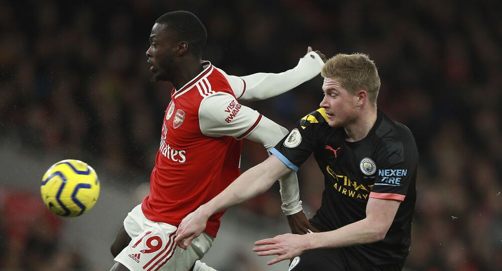 Arsenal's Nicolas Pepe, left, fights for the ball with Manchester City's Kevin De Bruyne during the English Premier League soccer match between Arsenal and Manchester City, at the Emirates Stadium in London, Sunday, Dec. 15, 2019.