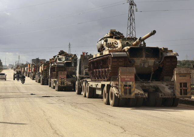 Turkish military convoy drives through the village of Binnish, in Idlib province, Syria, Saturday, Feb. 8, 2020