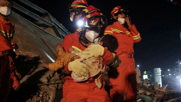 A worker wearing a face mask rescues a child at the site where a hotel being used for the coronavirus quarantine collapsed, in the southeast Chinese port city of Quanzhou, Fujian province, China March 8, 2020 - Sputnik International