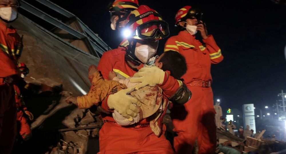 A worker wearing a face mask rescues a child at the site where a hotel being used for the coronavirus quarantine collapsed, in the southeast Chinese port city of Quanzhou, Fujian province, China March 8, 2020