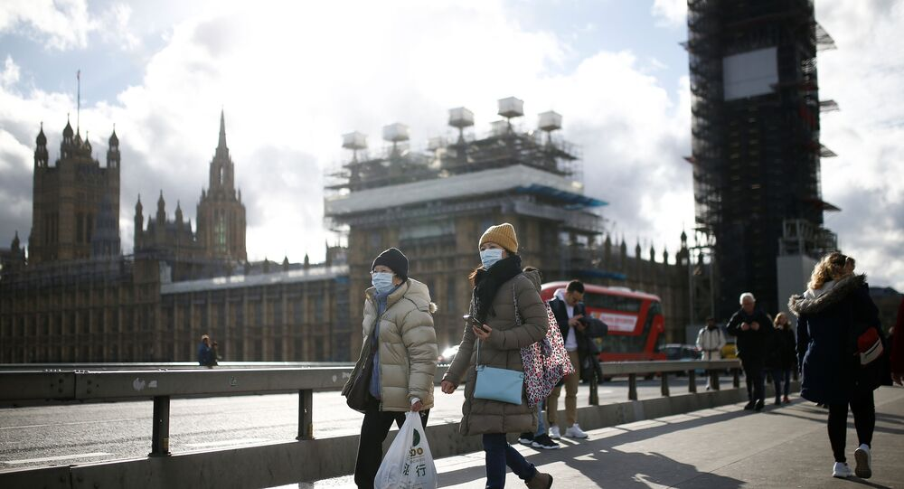 The Houses of Parliament can be seen as people wearing protective face masks walk across Westminster Bridge