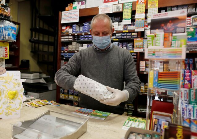 A vendor wearing a protective face mask works in a Tobacco Store on the second day of an unprecedented lockdown across all of the country