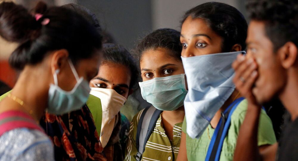 A group of students wearing protective masks wait to buy tickets at a railway station amid coronavirus fears, in Kochi, India, March 10, 2020.
