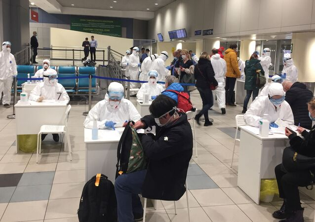 Russian officials and medical staff wearing protective gear check passengers as a preventive measure against the coronavirus (COVID-19) at Moscow's Domodedovo Airport