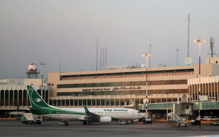 Iraqi airways aircraft is parked next to the building of the International airport of Baghdad, Iraq.