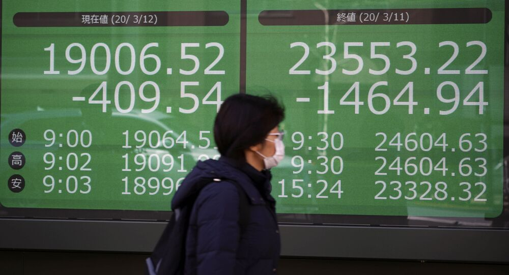 A woman walks past an electronic stock board showing Japan's Nikkei 225 and New York Dow index at a securities firm in Tokyo Thursday, March 12, 2020