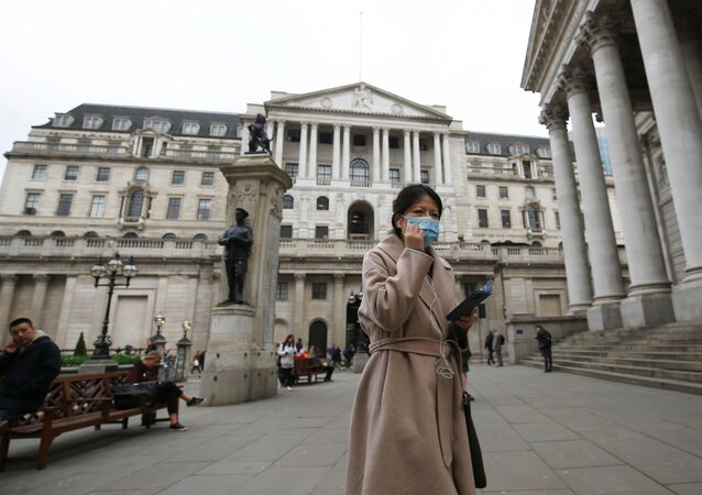 A woman, wearing a protective face mask, walks in front of the Bank of England, following an outbreak of the coronavirus, in London, Britain March 11, 2020