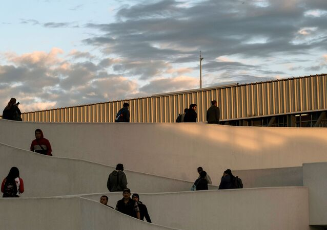 People walk towards to the United States at El Chaparral crossing port on the US/Mexico Border in Tijuana, Baja California state, Mexico, on February 29, 2020