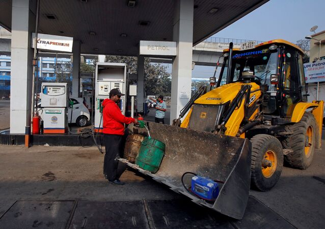 A worker fills diesel in a container at a fuel station in Kolkata