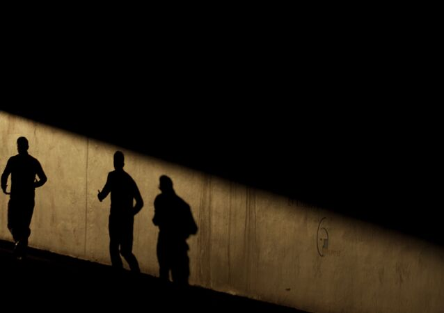 Two Men Cast Their Shadows on a Wall