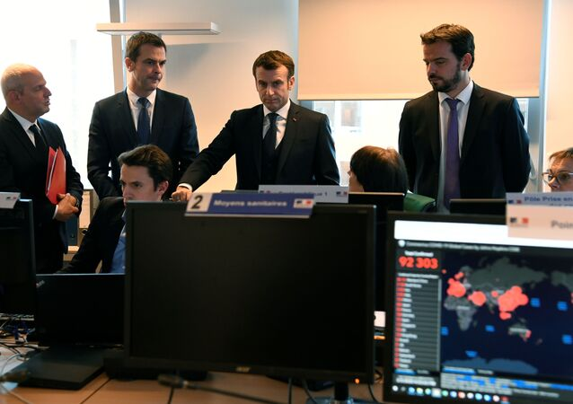 French President Emmanuel Macron (2R) flanked by Health and Solidarity Minister Olivier Veran (2L) and Director General of Health Jerome Salomon (L) visits the CORRUSS center