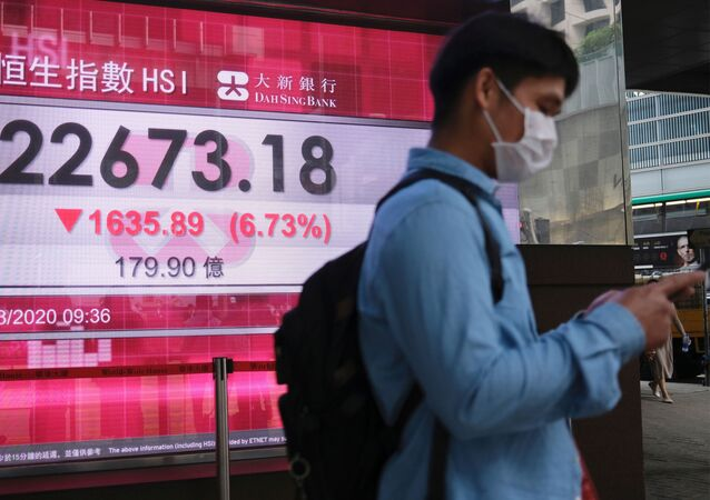 A man wears a protective mask as he walk past a panel displaying the Hang Seng Index during morning trading