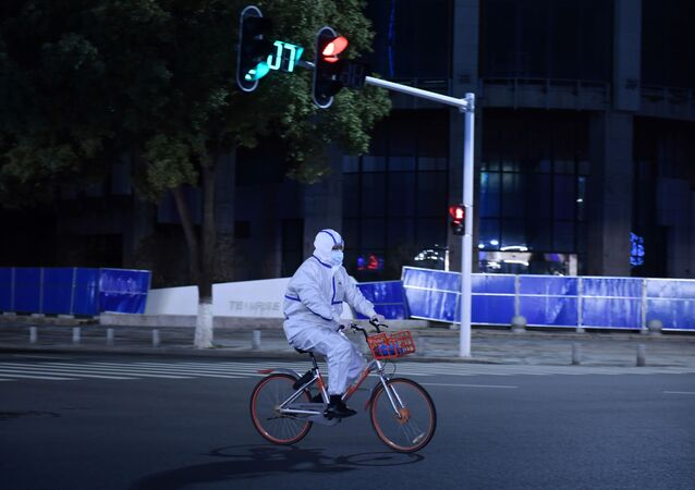 A man in a protective suit rides a shared bicycle at an intersection in Wuhan