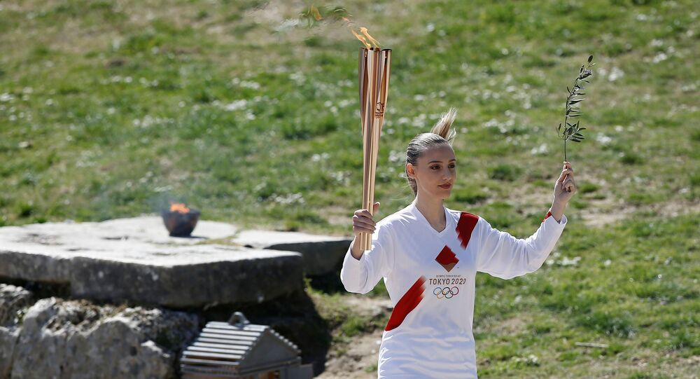 Olympics - Lighting ceremony of the Olympic flame for Tokyo 2020 - Ancient Olympia, Olympia, Greece - March 12, 2020  First torchbearer, Greek shooting athlete Anna Korakaki, carries the Olympic flame and the olive branch during the opening of the Olympic flame torch relay for the Tokyo 2020 Summer Olympics