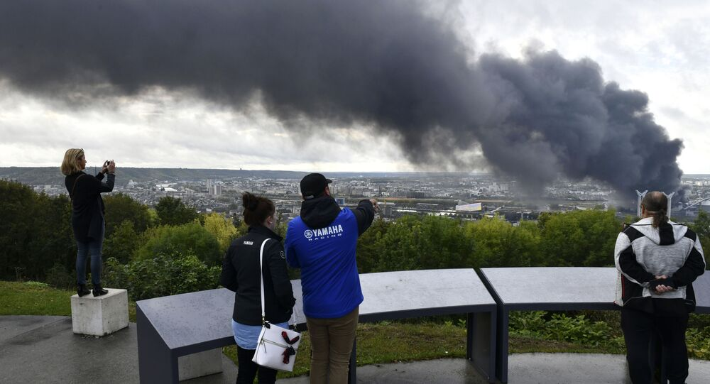 People watch black smoke rising after a fire broke at a chemical plant in Rouen, Normandy, Thursday, Sept.26, 2019