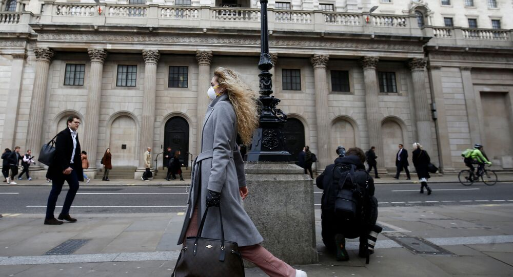A woman, wearing a protective face mask, walks in front of the Bank of England