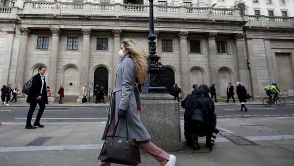 A woman, wearing a protective face mask, walks in front of the Bank of England - Sputnik International