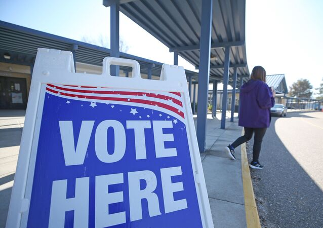 A Person Walks Past a Sign During a Runoff Election