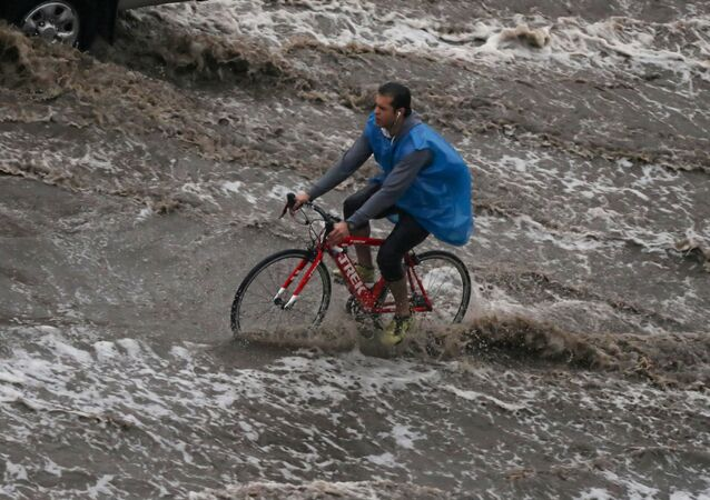 A man rides a bicycle during a thunderstorm and heavy rains in Cairo