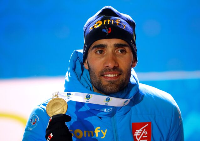 Martin Fourcade celebrates winning on the podium with his medal
