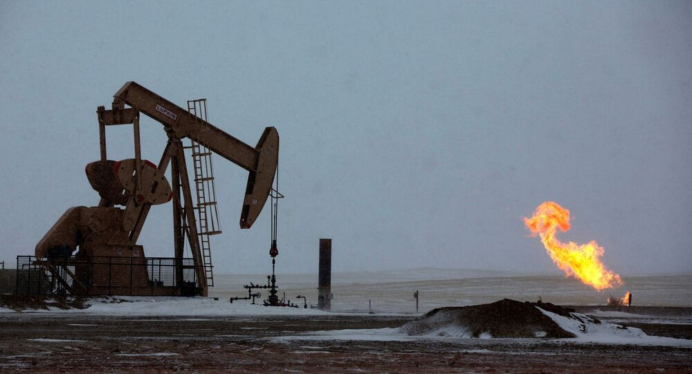 Natural gas flares are seen at an oil pump site outside of Williston, North Dakota