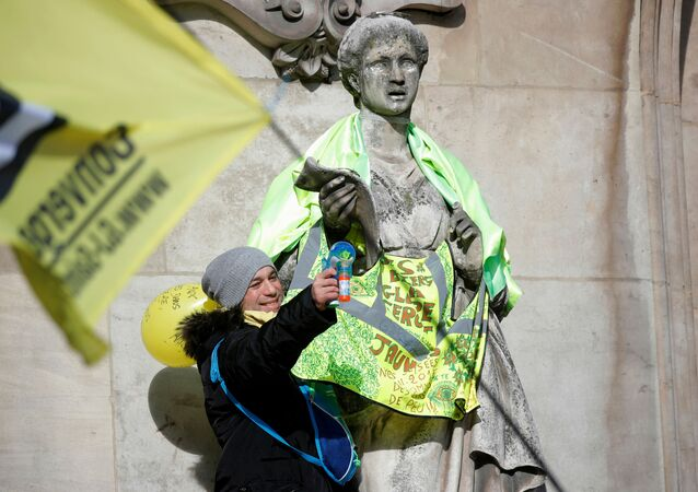 A protester stands next to a statue dressed in a yellow vest in front of the Opera Garnier during a demonstration before the opening debate on the French government's pensions reform bill at the National Assembly in Paris, France, 17 February 2020.