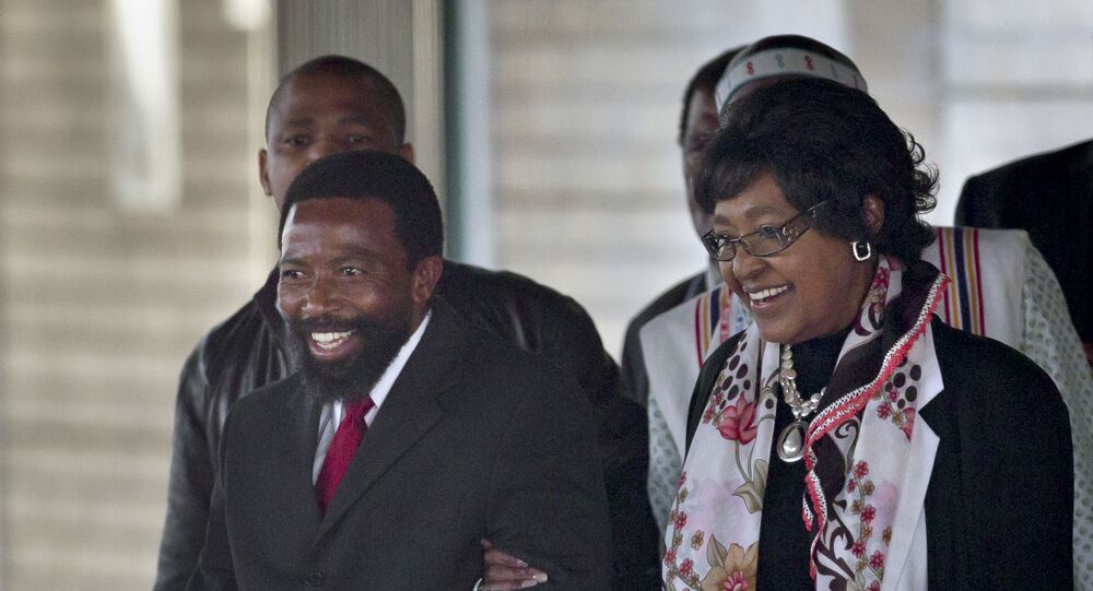 King Buyelekhaya Zwelibanzi Dalindyebo, left, the Xhosa king who rules the Thembu tribe to which the Mandela family belongs, escorts Nelson Mandela's former wife Winnie Madikizela-Mandela to her car, after they visited the Mediclinic Heart Hospital where former South African President Nelson Mandela is being treated in Pretoria, South Africa Tuesday, July 9, 2013.