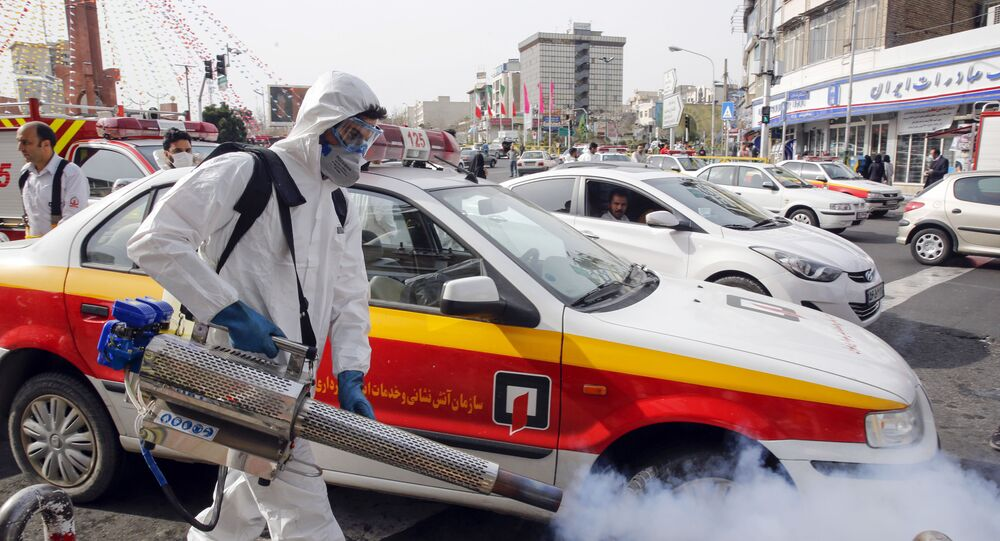 An Iranian firefighter disinfects a street in the capital Tehran in a bid to halt the wild spread of coronavirus on March 13 2020. - Iranian forces will clear the streets nationwide within 24 hours and all citizens will be checked for the new coronavirus in a bid to halt its spread, the military said