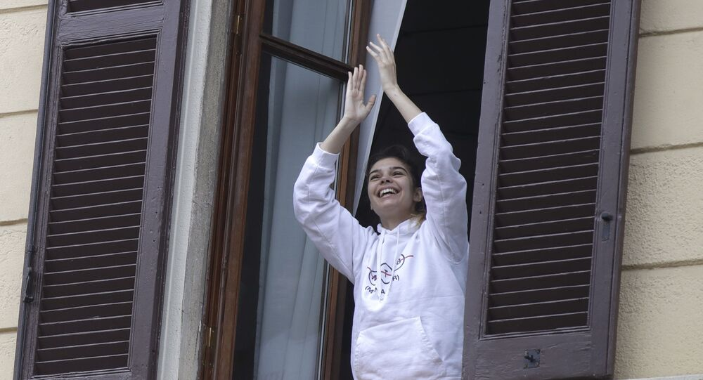 A girl leans out of a window to applaud in Milan