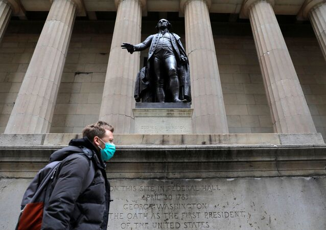 A man in a surgical mask walks in front of a statue of first US President George Washington