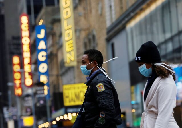 People in surgical masks walk through Manhattan's Broadway Theatre district