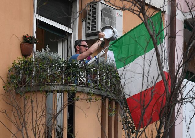 A man, next to an Italian flag, takes part in a flash mob to raise morale