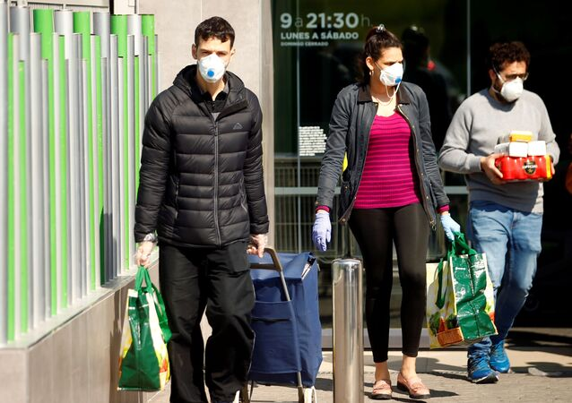 People wearing protective masks walk out of a supermarket, amidst concerns over Spain's coronavirus outbreak in central Madrid
