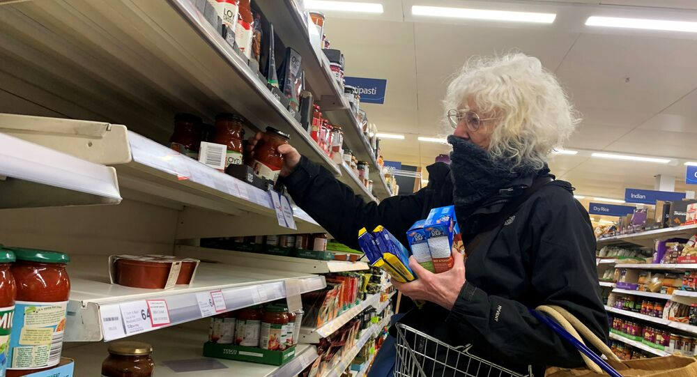 A shopper covers her face at a supermarket, as the number of coronavirus cases grow around the world, in London, Britain March 15, 2020.